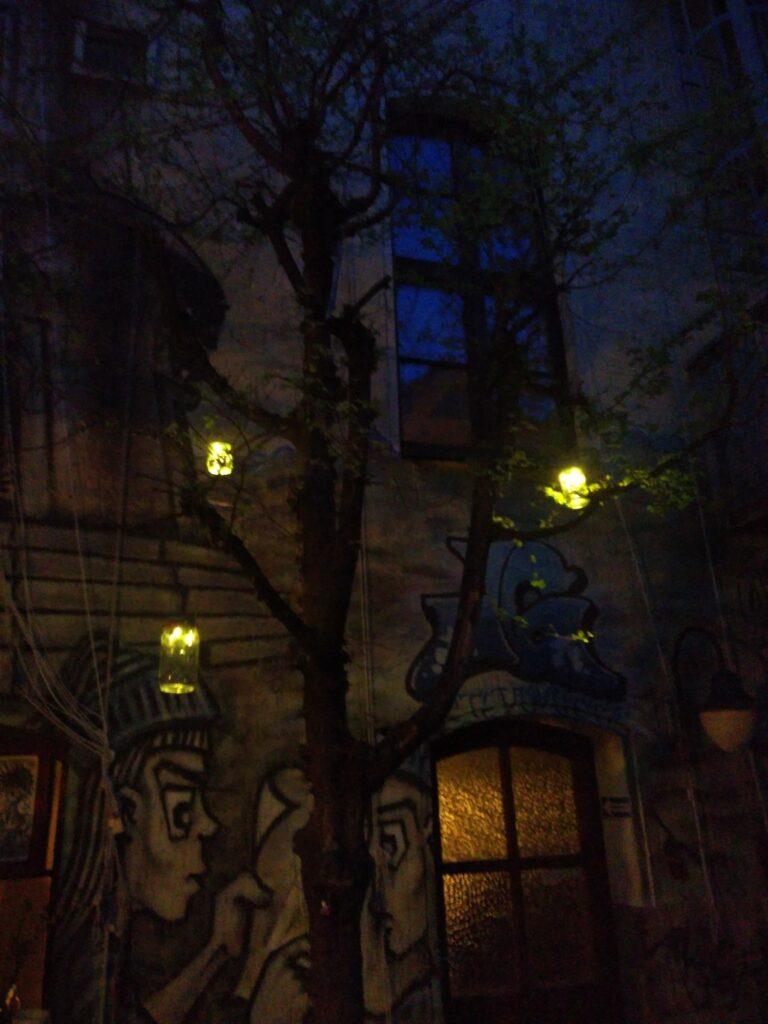 Dunkler Herbstabend mit Baum. Drei Lampen leuchten. Ein Grafitti an der Wand