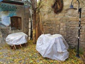 Auf dem Bild ist die Caféfläche der JG zu sehen. Zwei Tische sind zu sehen, diese sind mit Planen regenfest abgedeckt. Auf dem Boden liegt buntes Laub.